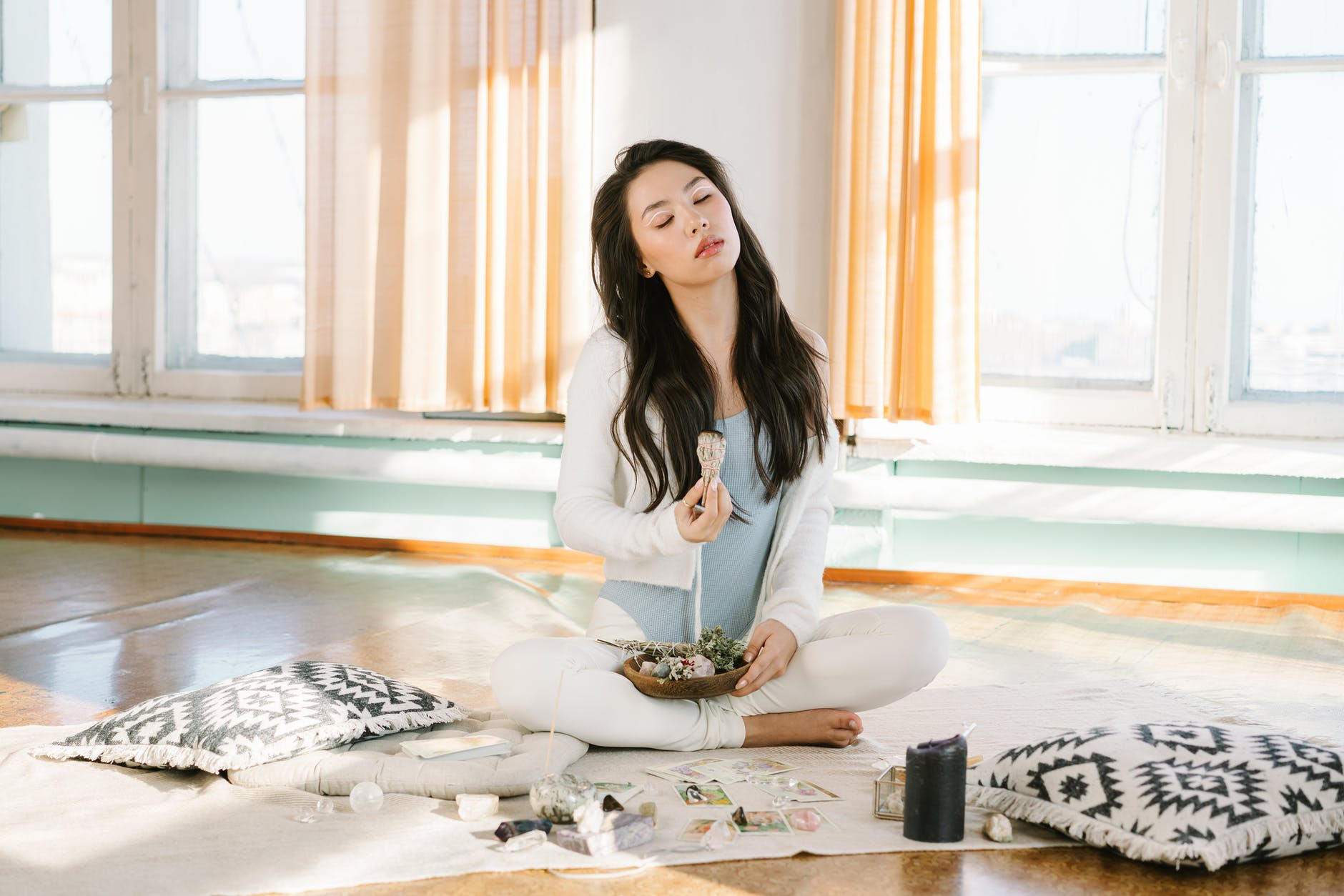serene asian woman meditating with sage smudge stick